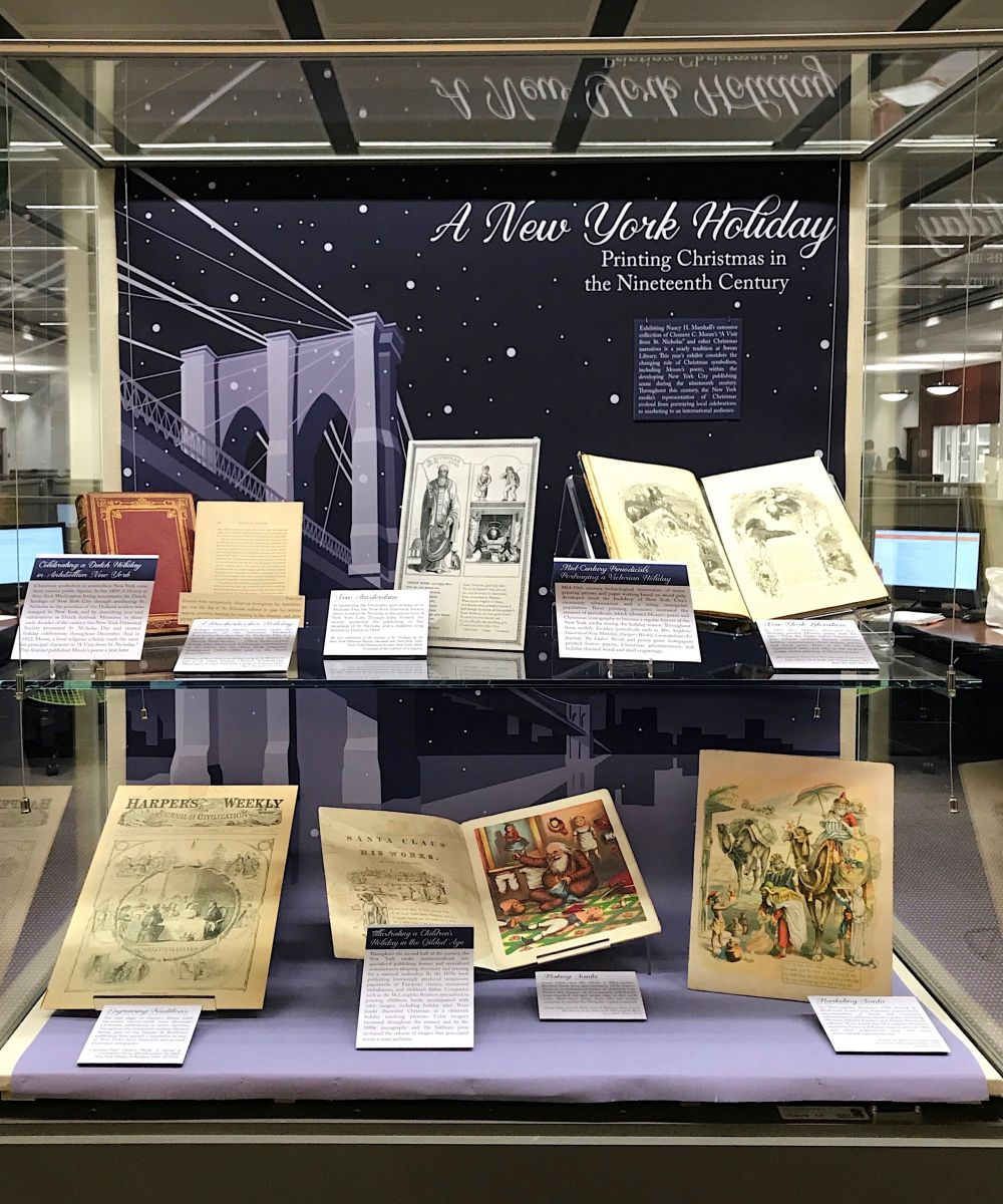 "Swem Lobby exhibit case, currently featuring ""A New York Holiday"" exhibit. The background of the exhibit case is indigo/purple with an geometric outline of the Brooklyn Bridge. On the upper and lower shelves of the display case are an assortment of illustrated prints -- excerpts from the volumes of the Nancy H. Marshall Collection."