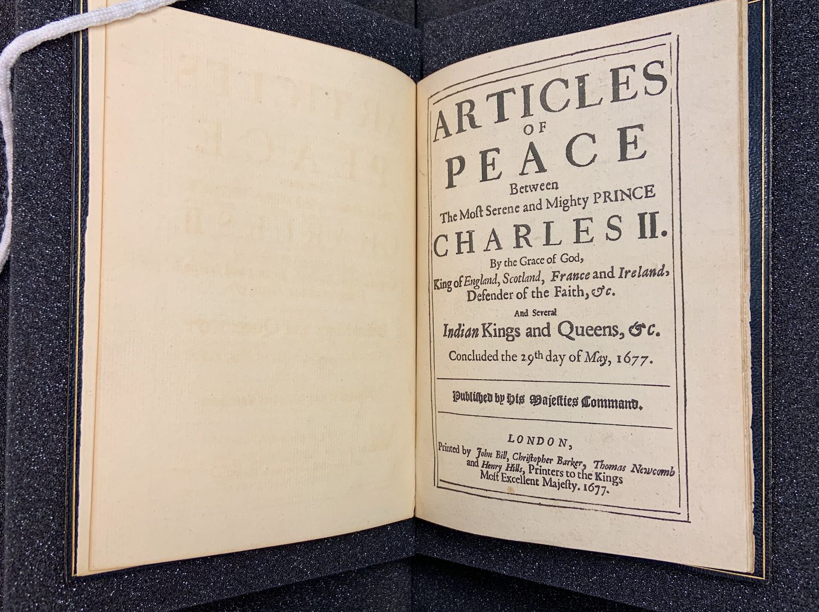 "A title-page spread of a short, small volume. Within a border outline on the right page, the title reads, ""Articles of Peace Between The Most Serene and Mighty PRINCE CHARLES II..."""