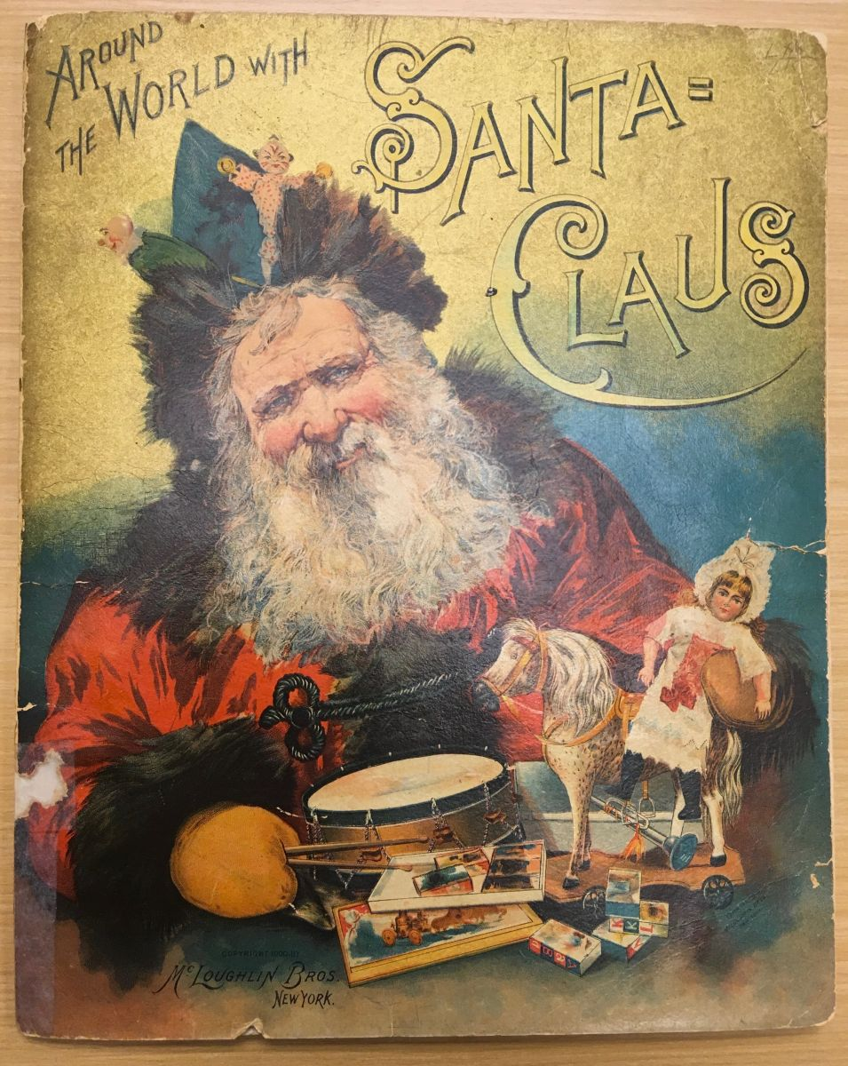 "Cover of ""Around the World with Santa Claus,"" featuring an illustration of Santa in a red cloak and a crown made of greenery. He holds an assortment of toys, including a doll, a horse figurine, and a drum."
