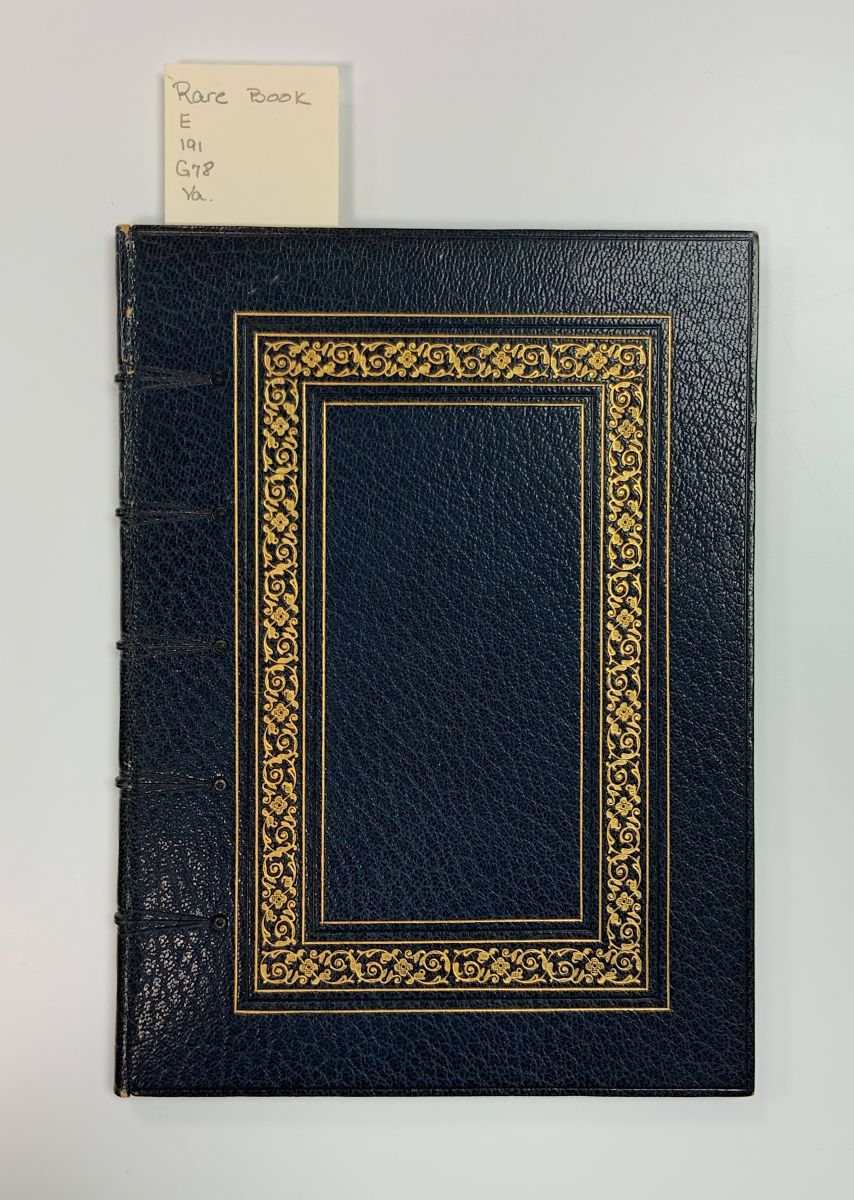 The exterior of Articles of Peace. A small, short blue volume with a gilded gold border within the interior of its cover.