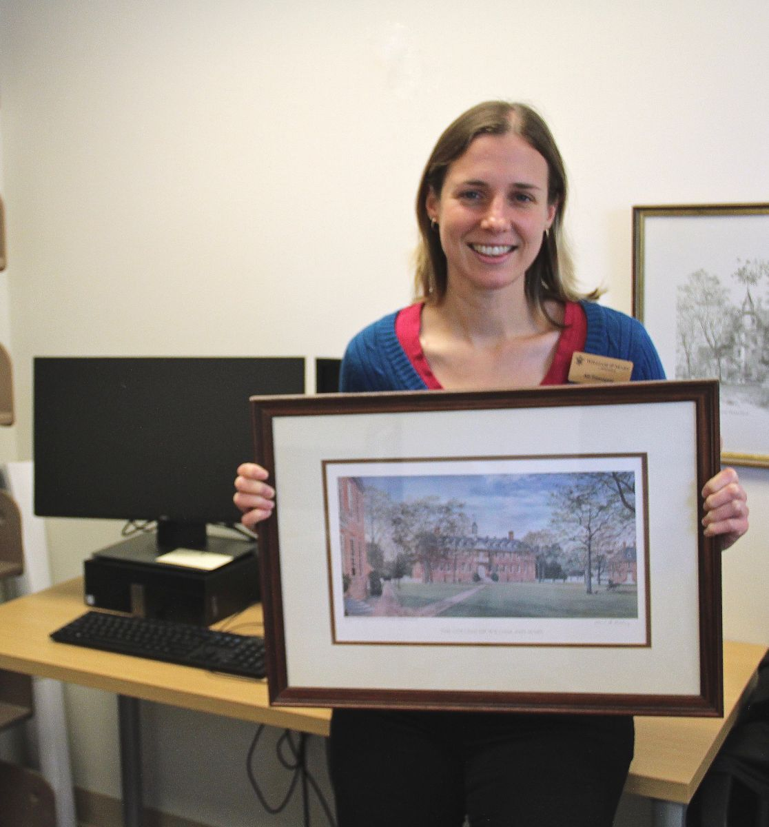 Ali Zawoyski stands and poses with a framed color print of the Wren Building.