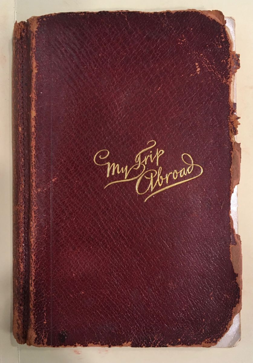 "Leather-bound diary with a red cover and gilded cursive text that reads, ""My Trip Abroad"""