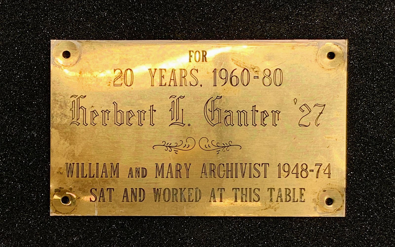 "Gold-colored plaque that reads, ""For / 20 Years, 1960-80 / Herbert L. Ganter '27 / William and Mary Archivist 1948-74 / Sat and Worked at the Table"""