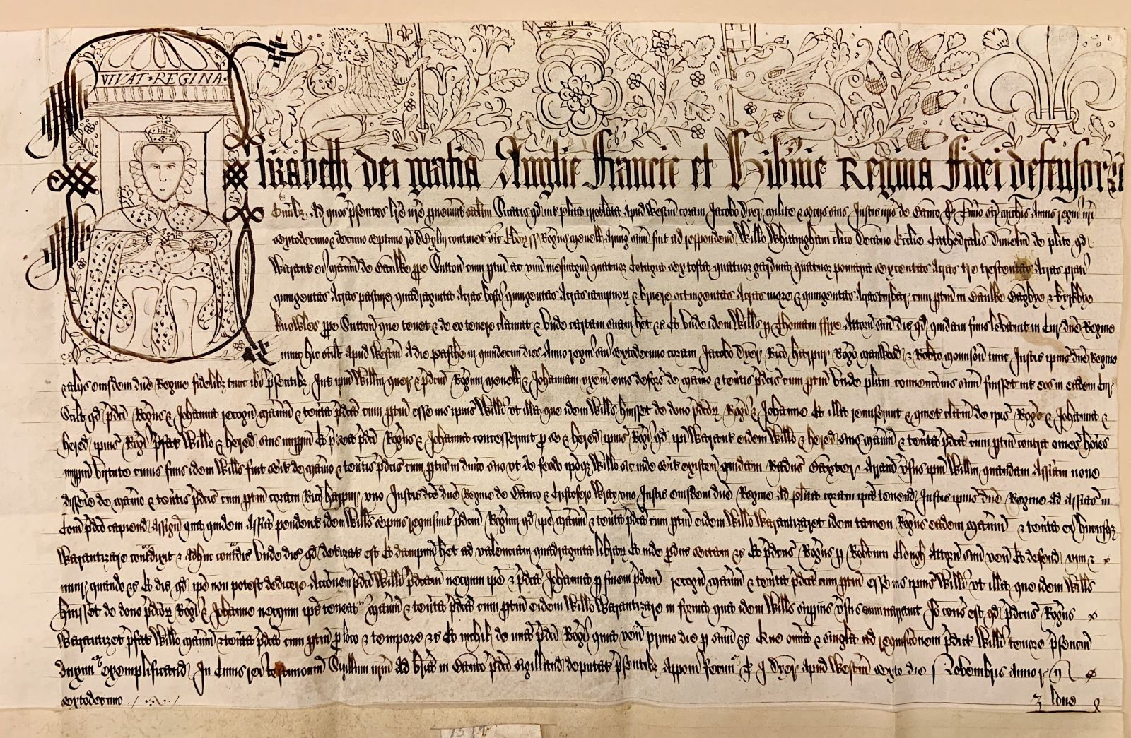 A view of the entire manuscript. The document is in a landscape orientation (shorter than it is wide). The majority of the document is filled with text, save for the portrait of Elizabeth I in the top-left corner and the border of illustrated symbols along the top margin.