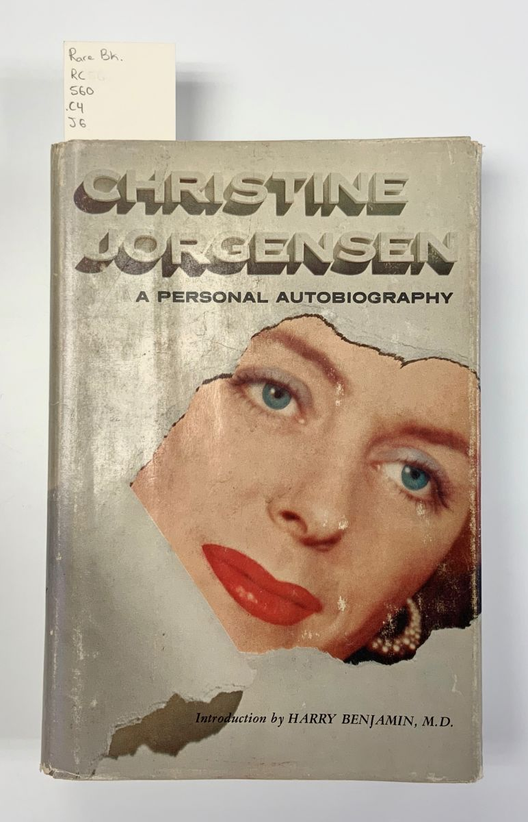 Cover of Christine Jorgensen: A Personal Autobiography. The dusk jacket is designed to look as if it has been torn. Through the tear, Jorgensen's face emerges.
