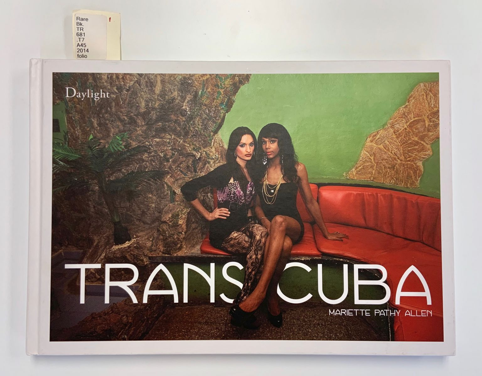 Cover of TransCuba, featuring two trans Cuban individuals sitting close together on a red sofa. The subjects stare at the camera and wear classy outfits, including layered jewelry.