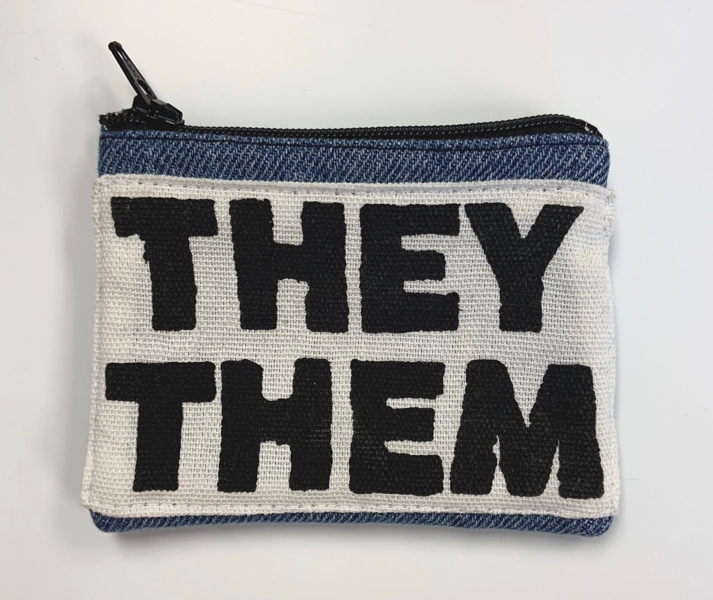 """Handmade blue denim zippered coin purse. A white stretch of fabric across the purse reads, """"THEY / THEM"""" in bold black lettering."""