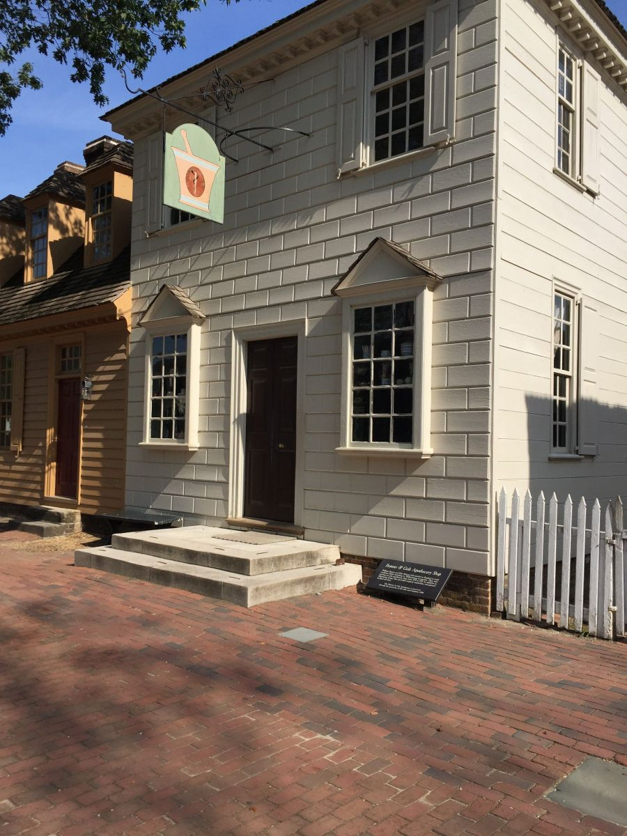 A white apothecary shop in historic Colonial Williamsburg, located along the pedestrian-only Duke of Gloucester Street.