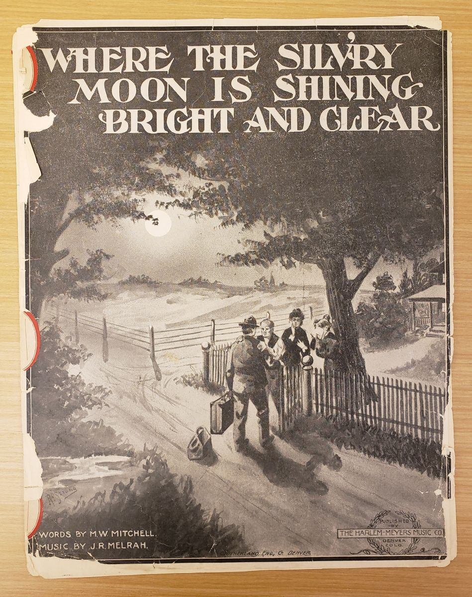 "A tattered sheet music cover features a brown and black picture of four figures standing by a gate. The two women are crying, while one man places his hands on the shoulders of the man with a suitcase. In the distance, the moon shines over some fields. At the top is the title, ""Where the Silv'ry Moon is Shining Bright and Clear"""