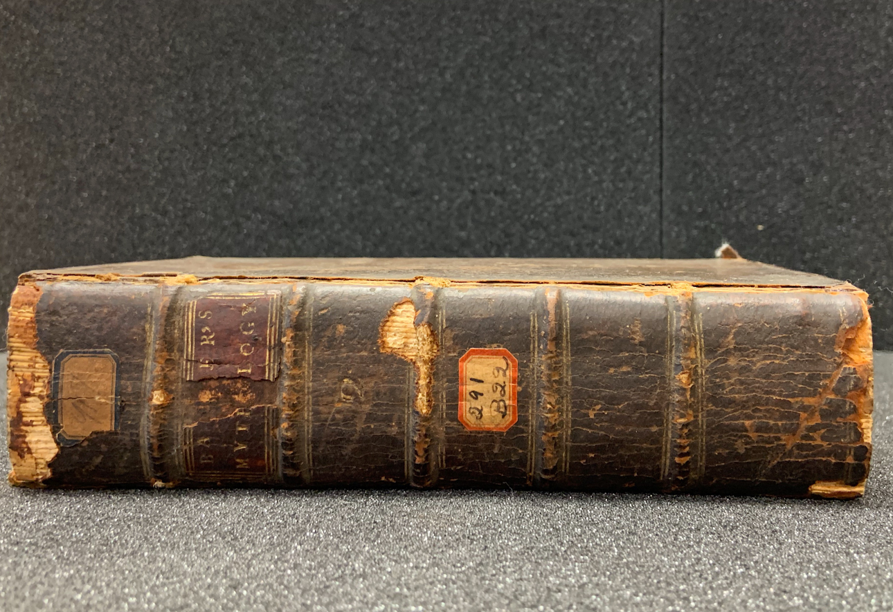 """The spine of Volume II of The Mythology. The leather spine is worn and cracked, its cover missing at the top to show the leaves of pages stacked and bound together. The title of the volume is in gilded lettering, barely readable due to age and damage. A sticker on the spine reads, """"291 B22,"""" perhaps an old call number. The book is laid flat on a foam support."""