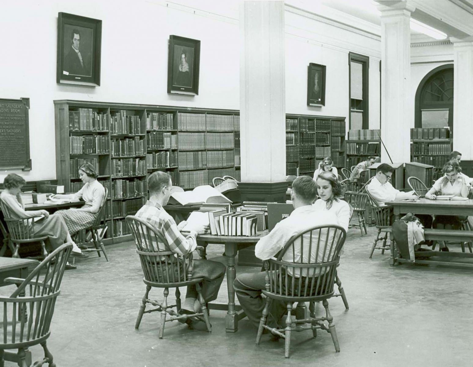 Students seated at round tables in the library at Tucker Hall.