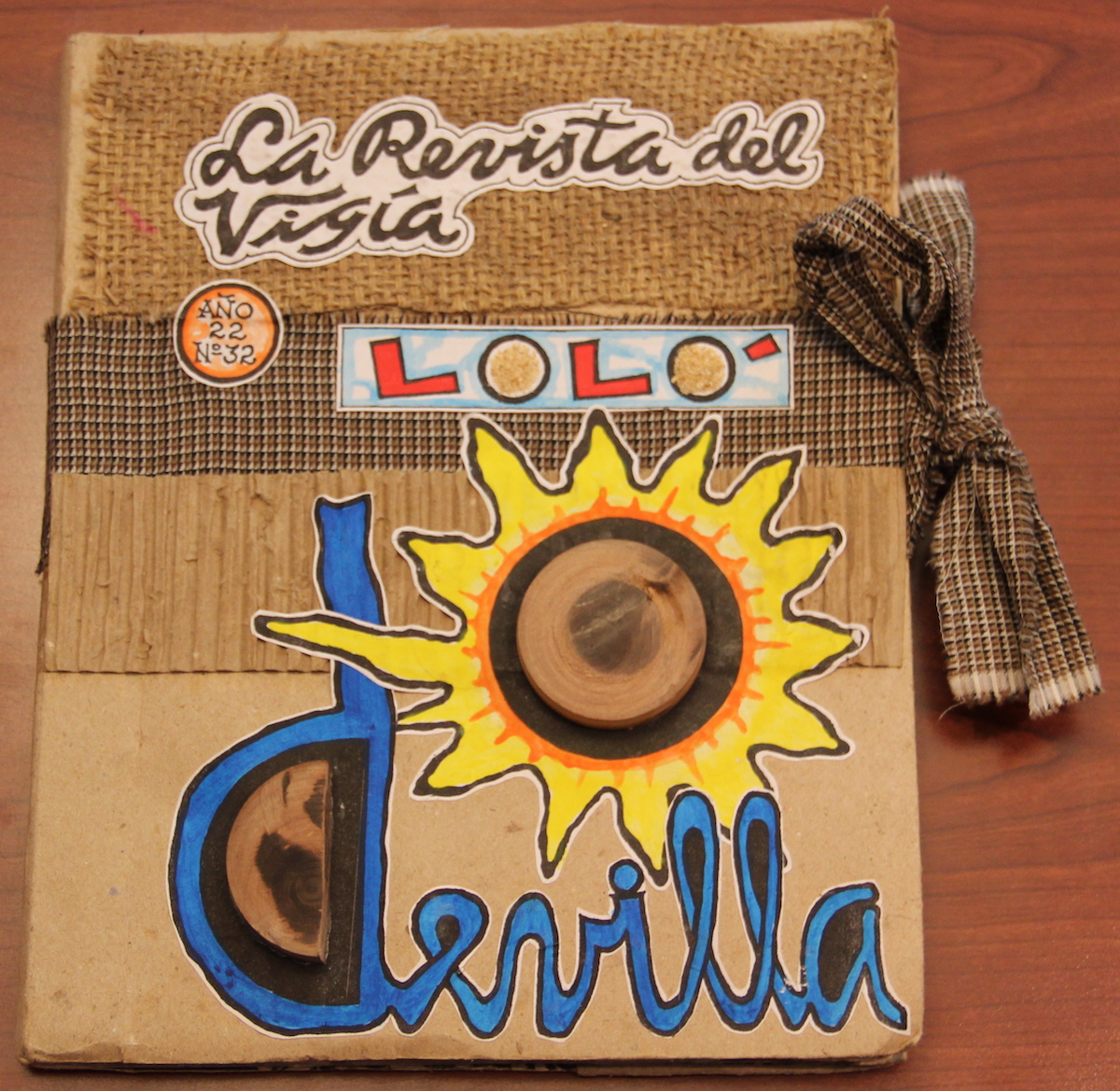"""Handmade book made from cardboard, burlap and painted paper cutouts with the title """"La Revista del Vigia""""."""