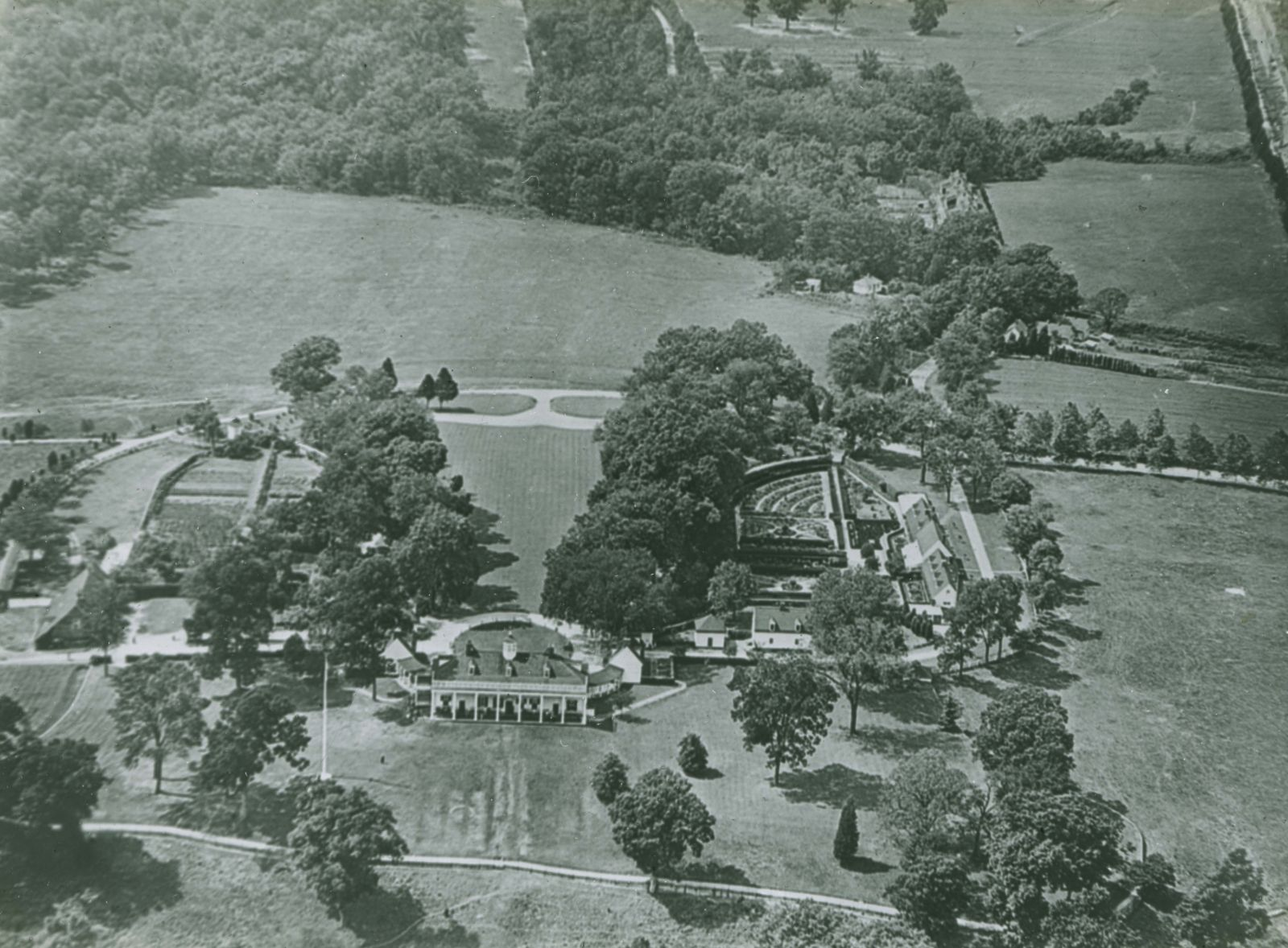 A black and white aerial photo shows the side of the Mansion with large pillars. On the right is a formal garden. Surrounding everything is farmland and woods.
