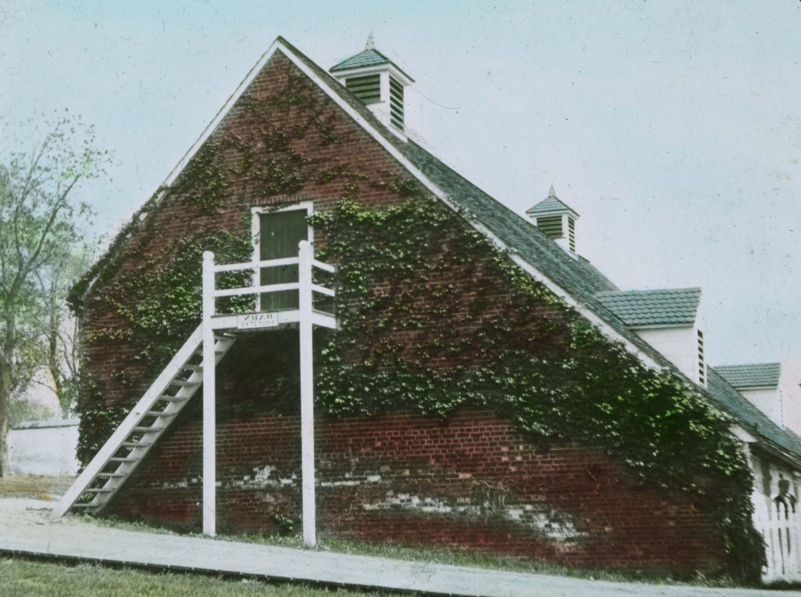 The brick wall of a red barn faces the viewer. Ivy crawls over the wall and around a door situated on the second story of the barn, from which lead white steps down the ground.