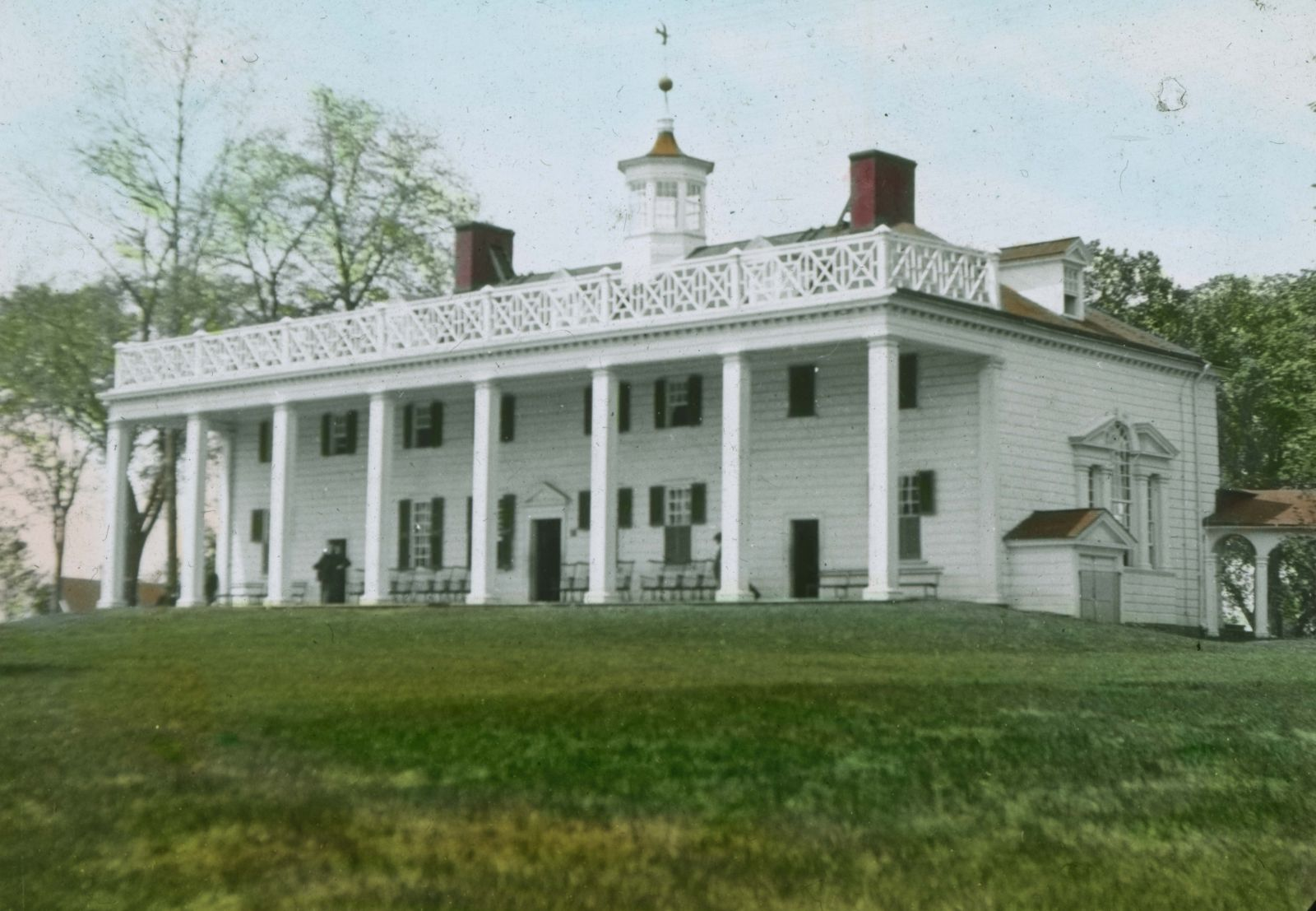 This colored slide of the Mount Vernon Mansion shows a very white house with green shutters and very red chimneys. This side of the house has a long portico with huge columns and a railing on the roof.