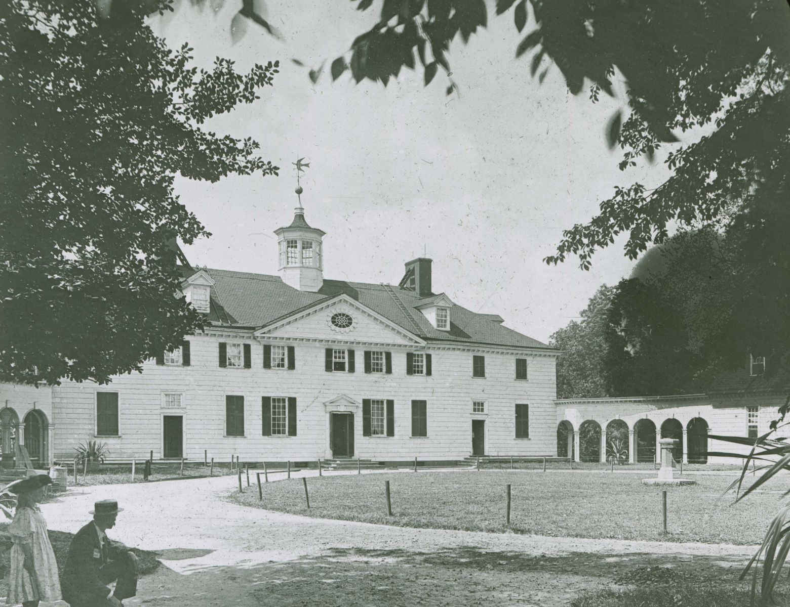 A black and white photo of the Mansion at Mount Vernon is taken from some trees to the left of the house. A man kneels, and a young girl stands beside him in the foreground of the picture.