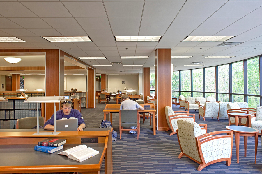 Students study at desks and open seating in the Wolf Law Library.
