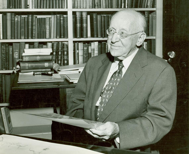 Earl Gregg Swem seated in front of bookshelves.