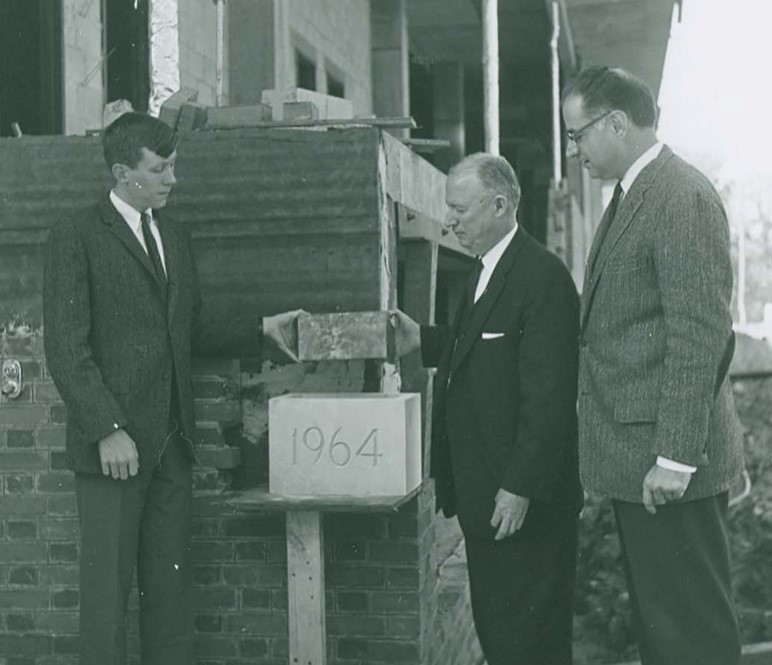 Three people display the cornerstone showing the date of Swem's construction.