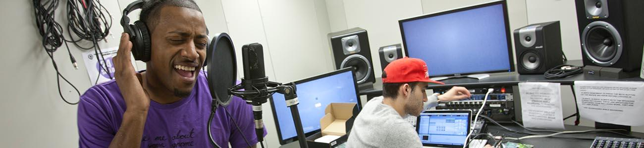 Two people in a media center studio - one at a mixing board and the other singing into a microphone