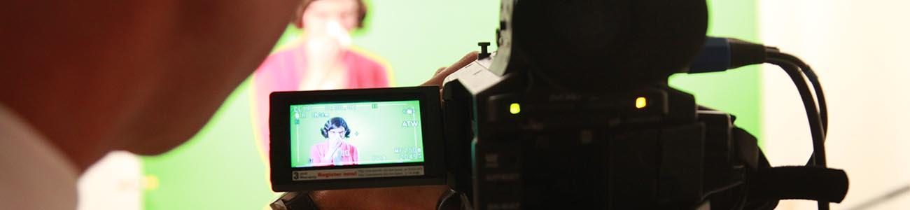 Person setting up a shot on a video camera with another person in the background in front of a green screen.