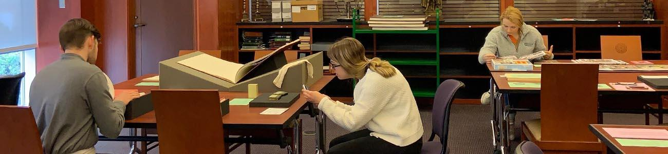 Patrons examining materials in the Special Collections reading room