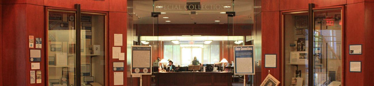 The entrance to Special Collections in Swem Library with two exhibit cases on either side of the glass entry doors