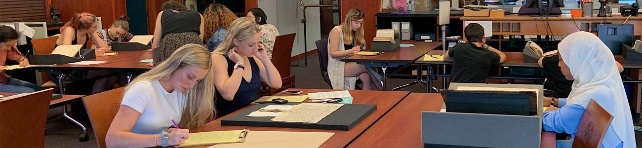 Students in a Renaissance studies class examine manuscripts in the Special Collections reading room.