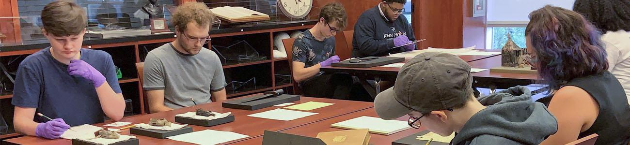 Class of students in the reading room examining artifacts from Special Collections.