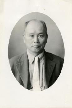Black-and-white photographic portrait (oval-shaped on white background) of an unidentified Chinese immigration applicant.