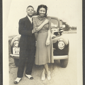"""Labeled """"Nat & Me at Yorktown,"""" this photo features a couple standing in front of their car with Williamsburg license plates, circa 1940."""