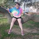 CeeCee in a tie-dye sweatshirt sitting in a tree with a big smile on their face