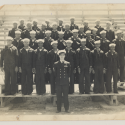 About 30 African American sailors stand in row formation for their photograph. A white lieutenant colonel stands in front of them.