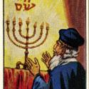 "Obverse of a ""Jewish Life in Many Lands"" trading card, featuring an individual standing before a fully-lit menorah. Hebrew script is above the menorah."