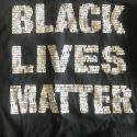 "Image of Shayna's black t-shirt with ""Black Lives Matter"" in white - zoomed in you can see the white text is made up of the names of all the black victims of police brutality."