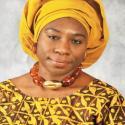 A headshot of Dr. Obasanjo, a black women, in a beautiful yellow headscarf