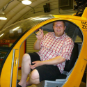 Alden - a man with short light hair - sitting in a yellow helicopter