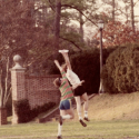 Photograph from the 1980s featuring two Ultimate Frisbee players reaching for a flying disc on the Sunken Garden.