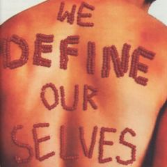 "Red beads strung into letters to form the text ""We Define Our Selves"" on a person's bare back"